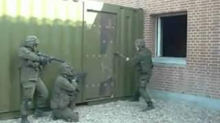 Un soldat ouvre une porte à coups de marteau