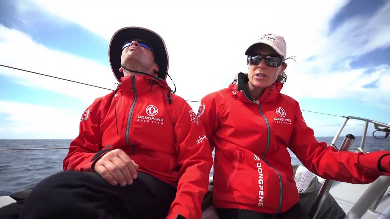 "Drone shots as Dongfeng sails under J0. Carolijn: Generally sail with 9 crew. Talks about positions: skipper, navigator, main trimmer, headsail trimmer, pitman, bowman. Talks about Daryl, their offshore helmsman at the moment. Instruments, spray. Pascal reads out the sched on the PA. Carolijn talks about the navigator. ""Generally he wears glasses to look really smart, and make smart decisions about strategy."" Pascal at the nav station. Pascal: ""Lift, lift, lift; strong wind and lift all the time."" Kevin trimming the main. Grinding. Carolijn narrates about Kevin adjusting the mainsheet. Talks about the combo of main and headsail trim, and coordination with the helm. Closeup of Kevin easing the mainsheet. Drone shot. Carolijn talks about the pit. ""We call it the piano."" Pitman organizes and coordinates between the front and back of the boat. Closeup of the pit controls. She talks about trimming the headsail. ""If it gets to hard I ask Horace for help and we grind with two."" She explains about trim. ""At the pointy end of the boat we have the bowman. They live at the front there, and they have a very busy job. It's a very hard job because it's the wettest part of the boat and you need a lot of strength to get things done.... Kevin is Speedy Gonzalez."" Drone shots."