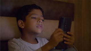 Cute young kid making a video call using a smartphone in his dark bedroom
