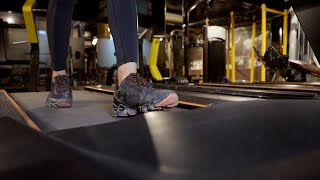 A modern girl wearing black shoes running on treadmill at the gym