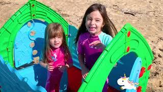Laurinha e Helena brincando de casa de brinquedo para crianças na praia