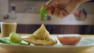 Hands of a woman decorating samosa plate with a coriander leaf at home in India