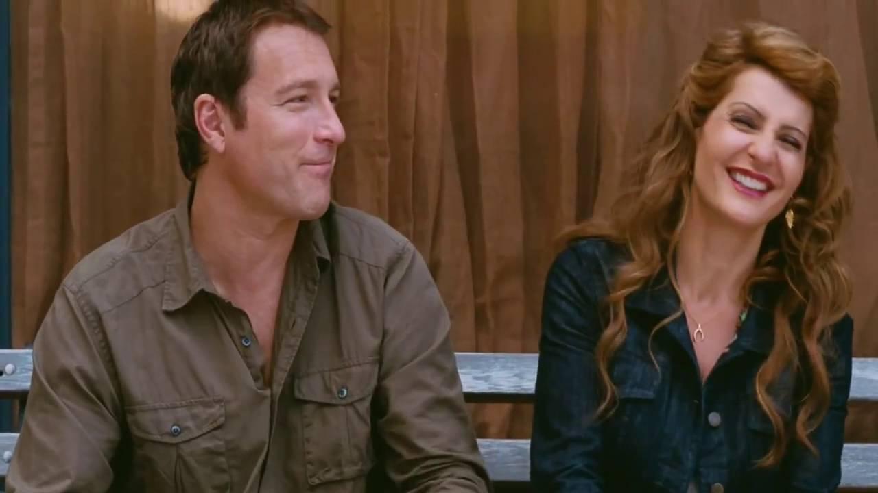 Greg e Genevieve ridono felici seduti su una panchina.