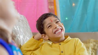 Raksha Bandhan - A young and naughty boy laughing with his sister on Rakhi festival