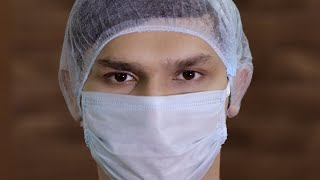 Extreme close up of a young doctor wearing a surgical mask and a medical cap