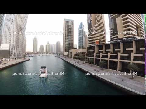 The waterfront Dubai Marina with a promenade where walking tourists and marine canal where sailing