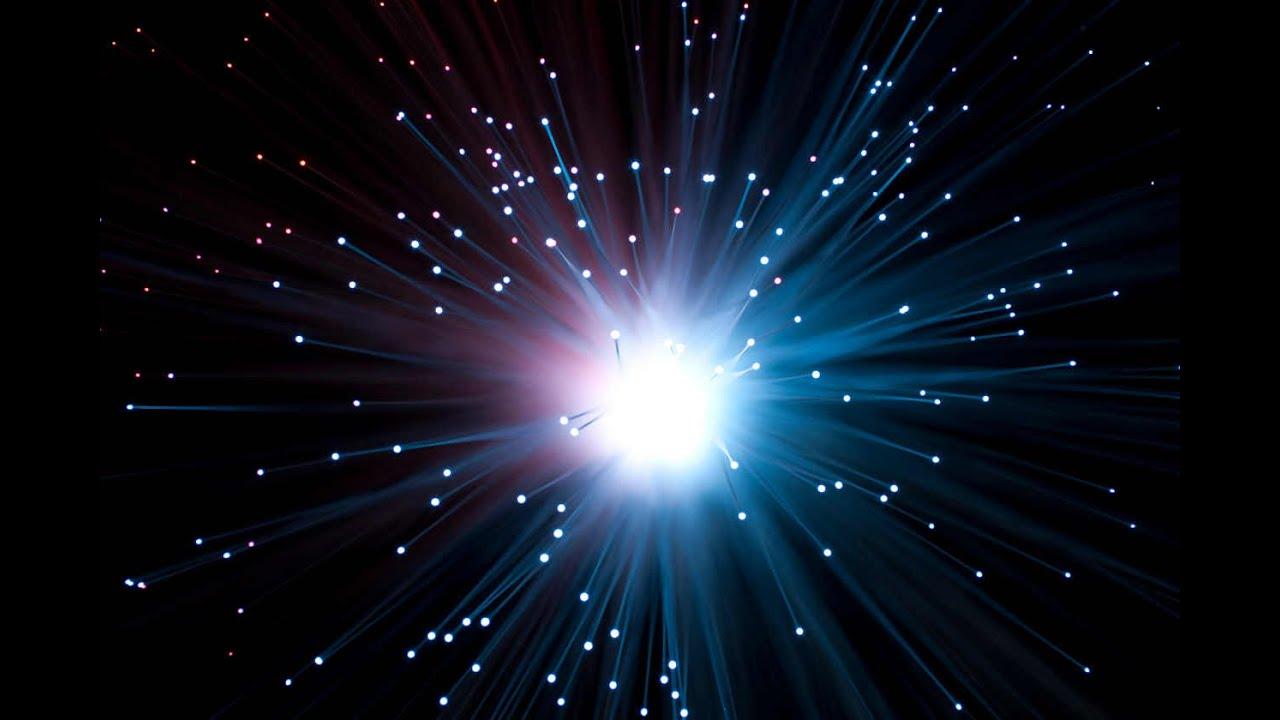 En la imagen se ve la representación de la explosión del Big Bang; se muestra un masa de la que se desprenden diferentes átomos a partir de rayos que muestran la expulsión de estos. La imagen se encuentra en colores negro que representan este espacio; blanca que evidencia la masa que dio origen al big bang y las partículas que se desprendieron y de azul y morado la explosión como tal.