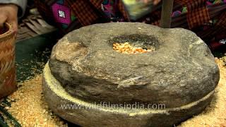 Bhutanese making corn Kharang using the traditional Rock Grinder