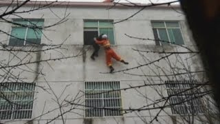 Dramatic rescue footage: Firefighters grab woman about to jump off building