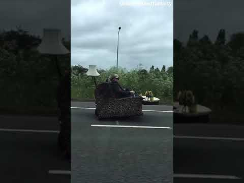 Curtis - Couple Is Seen Rolling Down The Highway On A Couch With Wheels