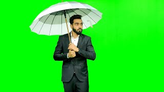 Man dressed formally opens up an umbrella in rain against the green screen