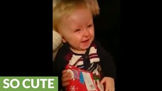 Gift-opening baby has a contagious case of the giggles