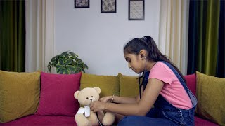 Beautiful Indian girl playing with a stethoscope and a cute teddy bear at home