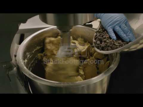 Close up panning shot of woman placing chocolate chips in bakery mixer