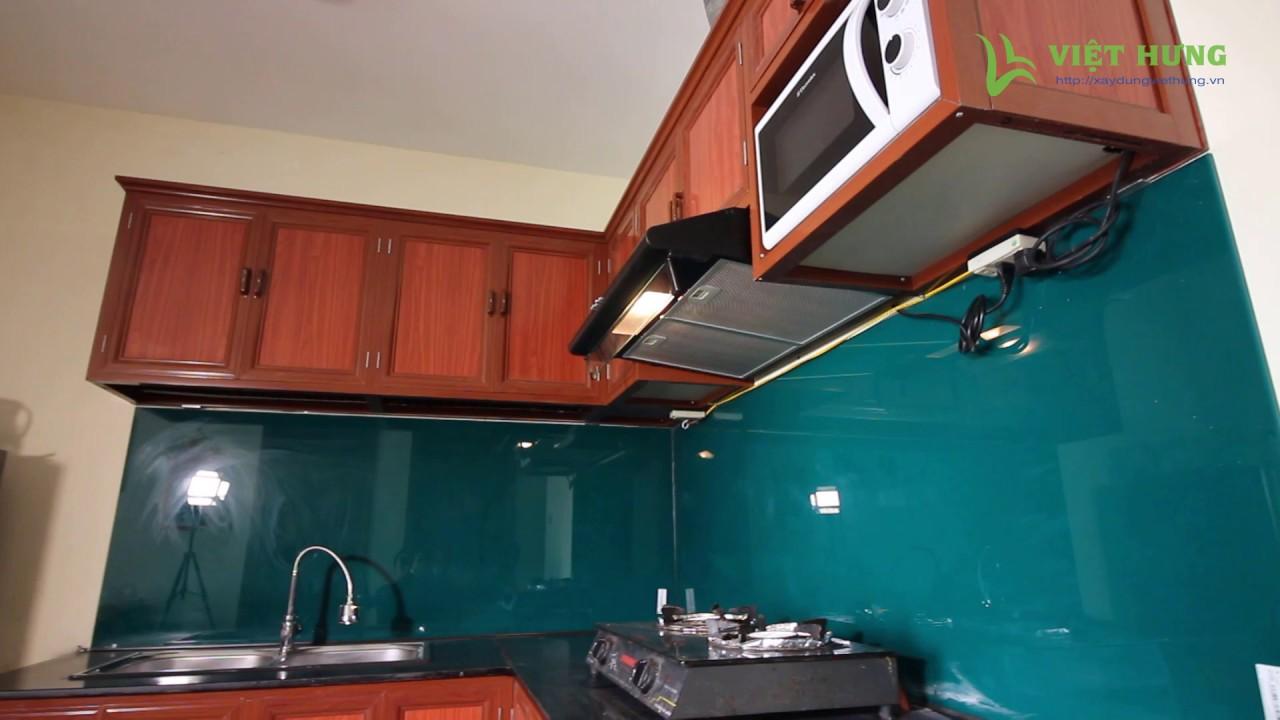 Tủ bếp nhôm kính sơn tĩnh điện màu vân gỗ hình chữ L, Kính cường lực ốp bếp