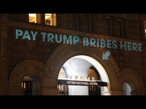 'Pay bribes here' sign projected onto Trump...