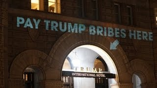 'Pay bribes here' sign projected onto Trump