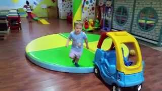 Indoor playground. Funny children run, jump and play with toys :horses, trains, balls, cars,