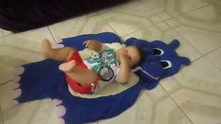 Lucas deitado em um tapete urso infantil