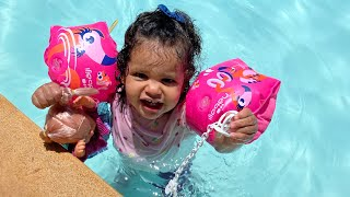 Little girl plays with her doll in the pool