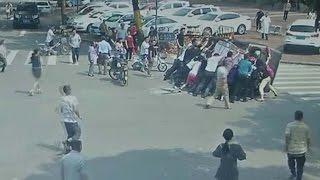 """""""فيديو"""" شاهد المارة يرفعون سيارة بعد انقلابها في حادث تصادم جنوب الصين"""