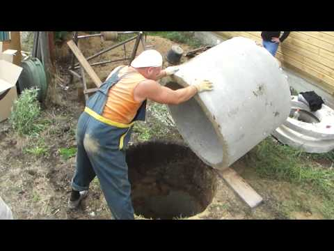 Загрузка бетонных колец в колодец.