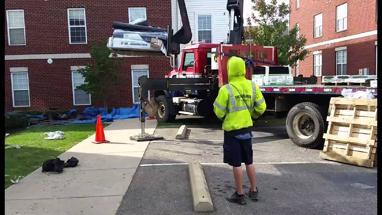 ABC Supply Crane Operator Moves Shingling To University Village Apartment  Roof