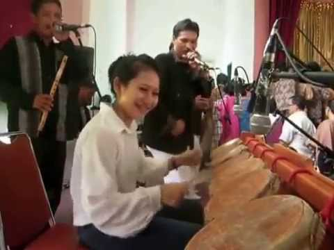 Cute Girl from Indonesian playing traditional drums from batak called TAGADING