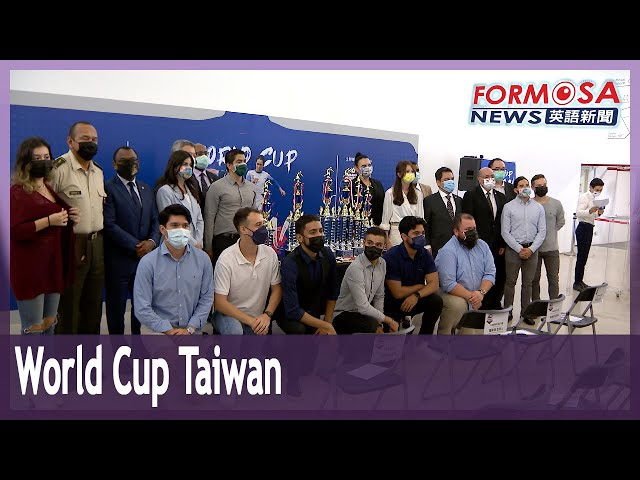 Ambassadors head onto the football pitch, before soccer's World Cup Taiwan kicks off