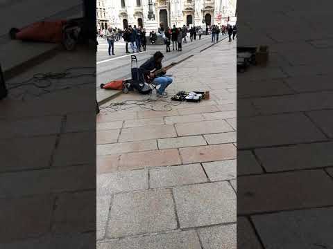 "Talented street artist perform ""the sound of silence "" with his guitar in Milan"