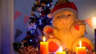 Tilt shot of a teddy bear surrounded by scented candles in a decorated room for Christmas