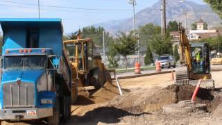 Blue dump truck dumping dirt then a Cat Scraper moving dirt into place on a road work site