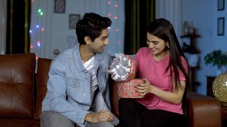 Handsome young guy gifting a Birthday or Valentines Day present to his girlfriend