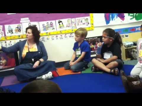 Preschool Teacher Reading A Book To The Class