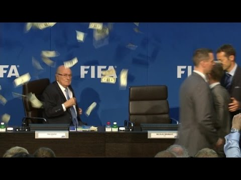 Comedian throws money at Blatter during press conference
