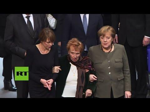 Merkel coge del brazo a una superviviente de Auschwitz para ayudarle ocupar su asiento