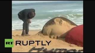 """شاهد.. """"فنان هندي"""" ينحت تشكيلاً لجثة الطفل السوري الغريق"""