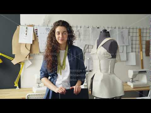 Portrait of beautiful young woman tailor standing in workplace near clothed mannequin and looking at