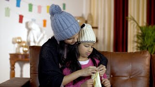 Closeup shot of an Indian mother teaching her daughter how to knit during wintertime