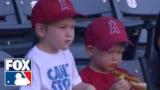 Kid struggles to eat a hot dog at baseball game