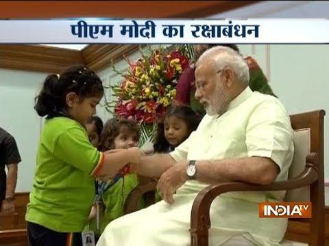 Children tie Rakhi to PM Narendra Modi on the occasion of Raksha Bandhan