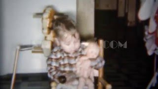 1962: Toddler boy feeding and kissing plastic baby doll.  STEEP FALLS, MAINE
