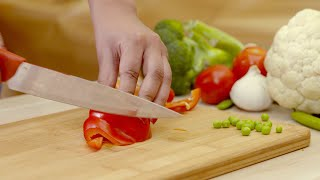 Close up shot of a girl's hands slicing red bell pepper on a wooden chopping board
