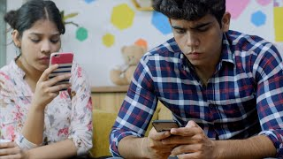 Young Indian couple ignoring each other and glued to their mobile phones