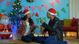 Young husband-wife in Santa hats happily enjoying their Christmas holiday