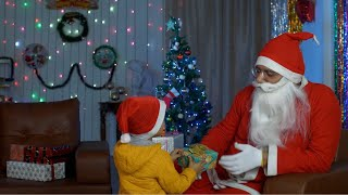 A young innocent kid giving a colorful gift to an old unhappy Santa during Christmas time