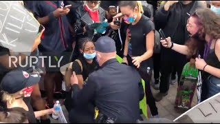 USA: Police officer kneels to hug protester at California rally
