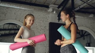 Attractive Girls Are Talking and Laughing in Large Modern Sports Center. Women Are Holding Colorful