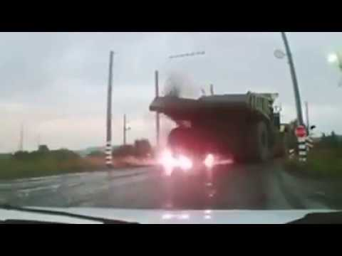 Huge mining dumptruck hits overhead electric wires causing the tyres to explode