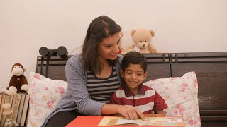 Pretty Indian mother and her son reading a storybook together - Nighttime stories at home